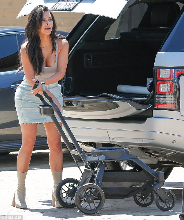 She's got her hands full! The Keeping Up with the Kardashians star didn't miss a beat as she set up the stroller in her skintight mini skirt and heeled boots