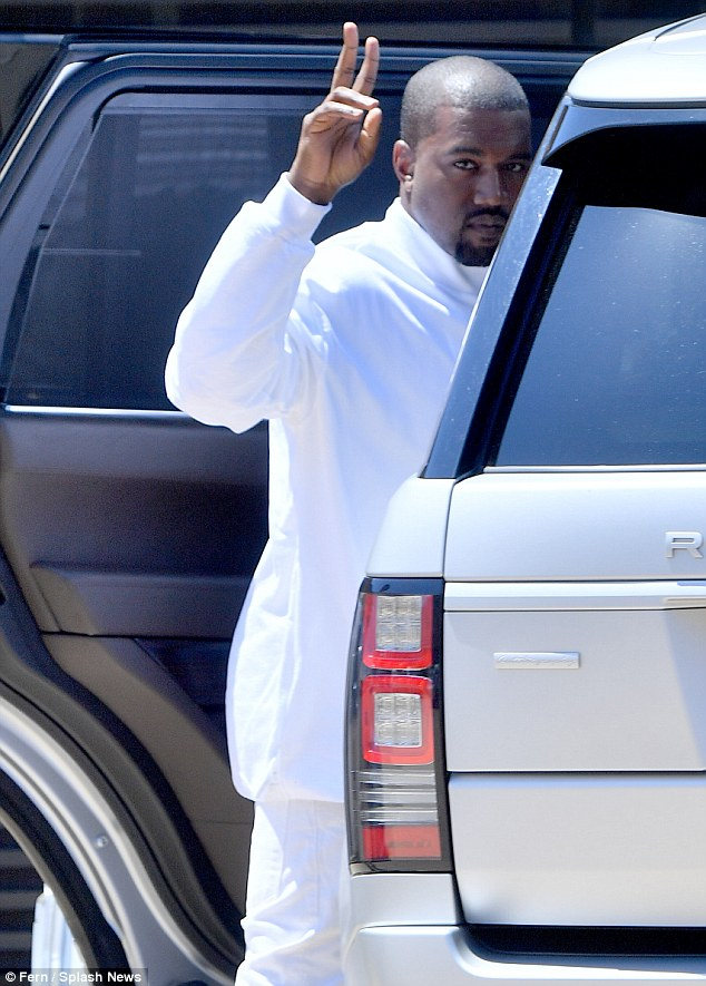 Happy to be here: Kanye looked to be in good spirits for his Father's Day brunch, flashing a peace sign to fans